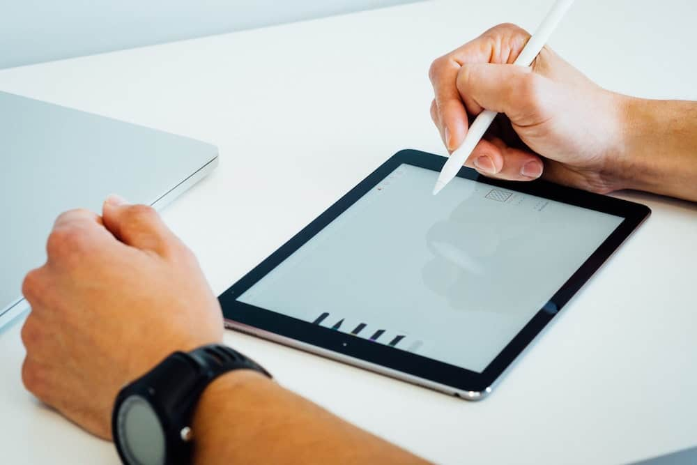 hands designing logo on electronic tablet