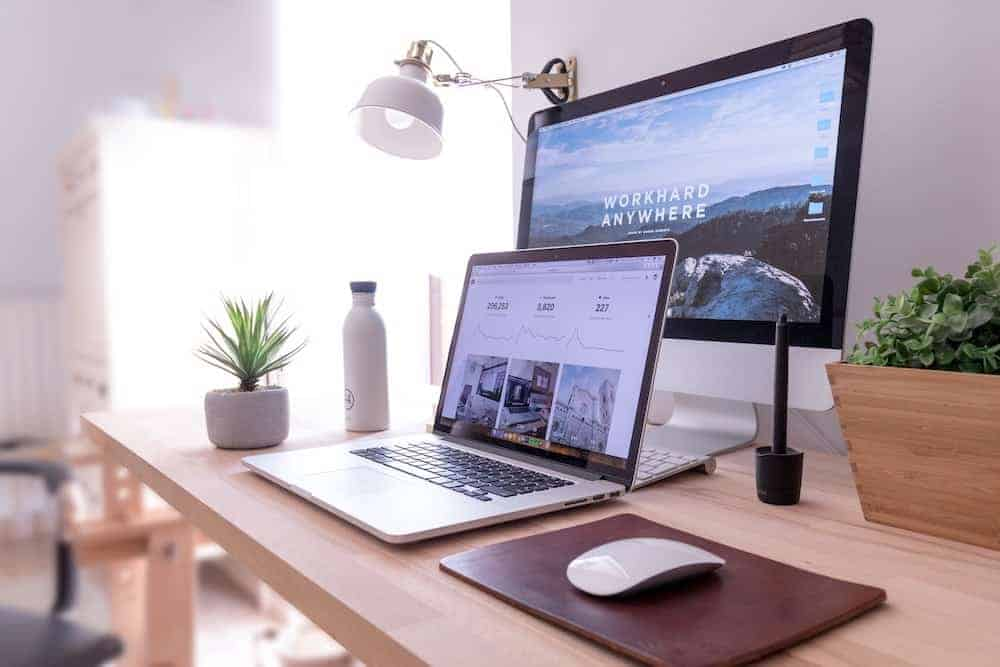 laptop displaying website alongside computer monitor