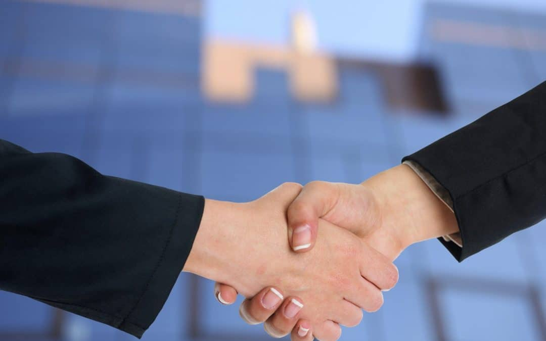 Two people shaking hands at a corporate networking event.