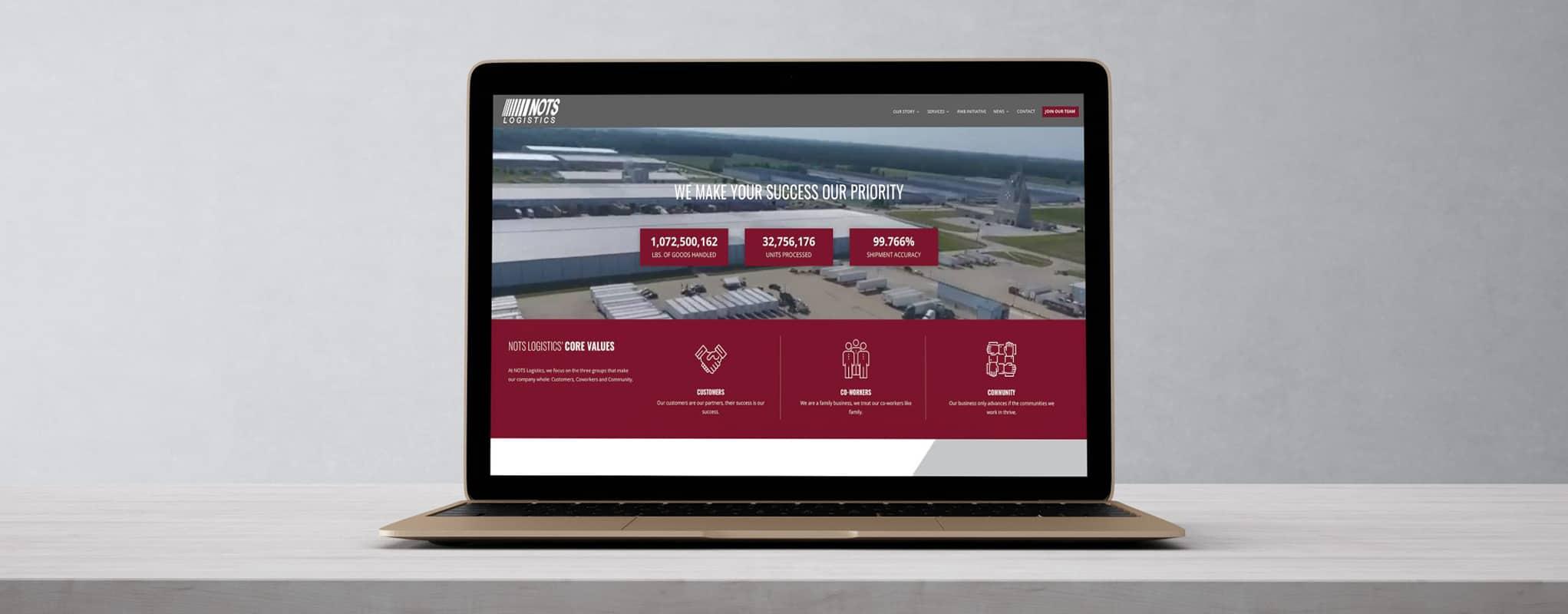 NOTS logistics website pulled up on laptop sitting on modern gray concrete desk