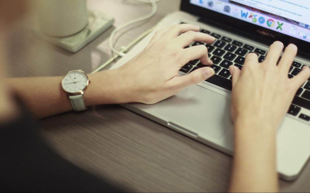 sets of hands typing a Google review on a laptop