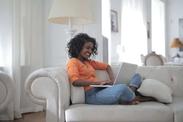 African American woman in an orange shirt Sitting On a white Couch Using Laptop