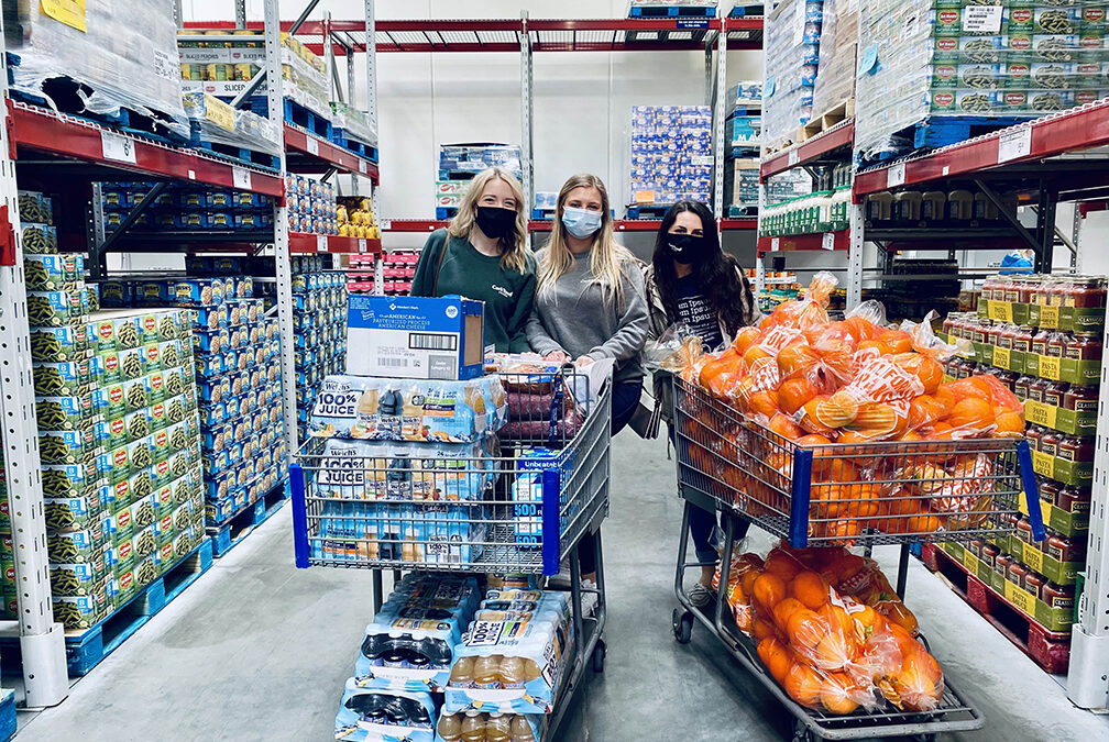 Three young girls wearing masks in Sams grocery store with two carts full of food to donate
